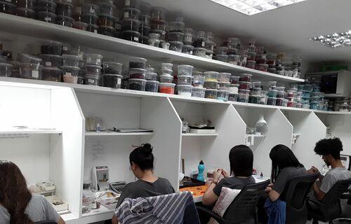 Trabalhadores em pequenas estações fazendo bijuterias. Foto: Cristiane Bonfanti