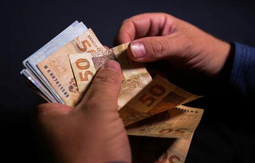 Mãos folheando cédulas de cinquenta reais. Foto: Marcello Casal Jr./Agência Braisl